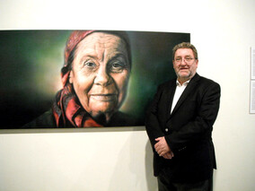 Exhibition curator Brian Easton beside painting of Joan Metge by Sofia Minson